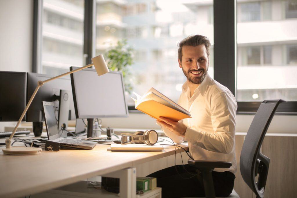 Man holding book in front of multiple monitors