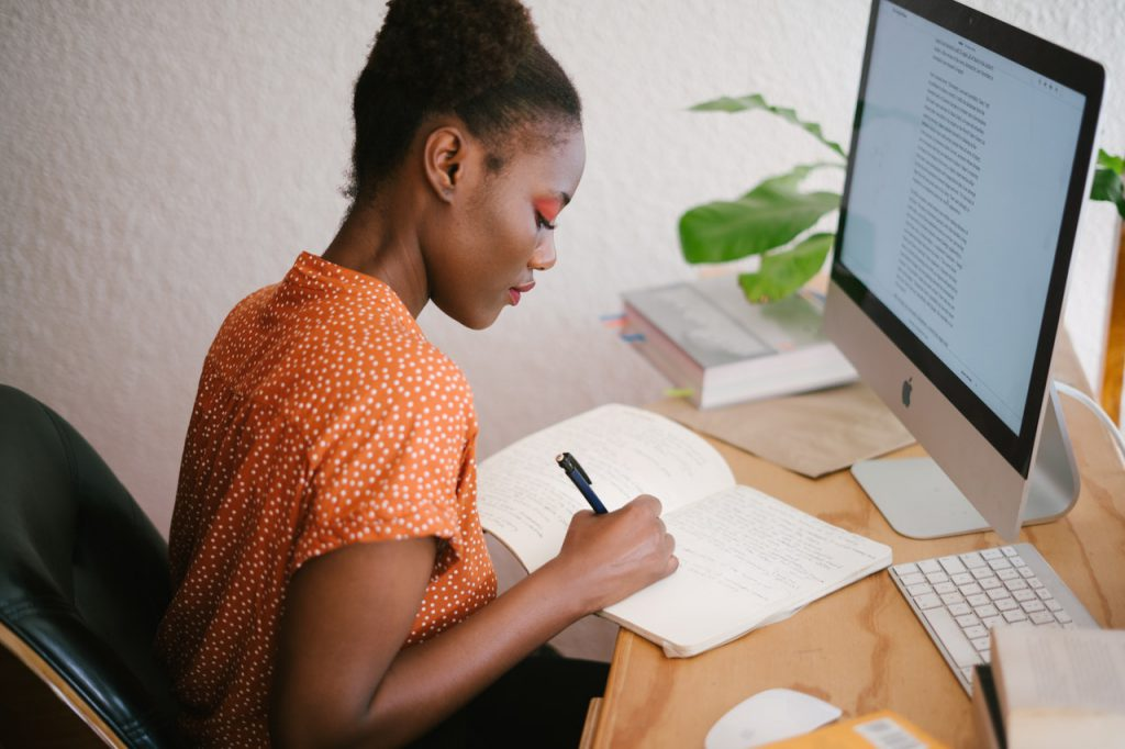 Woman in front of her computer writing