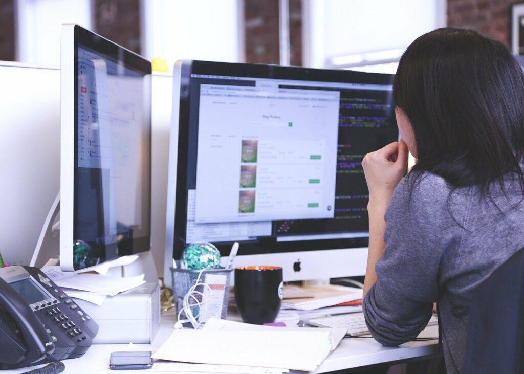 Woman using multiple monitors