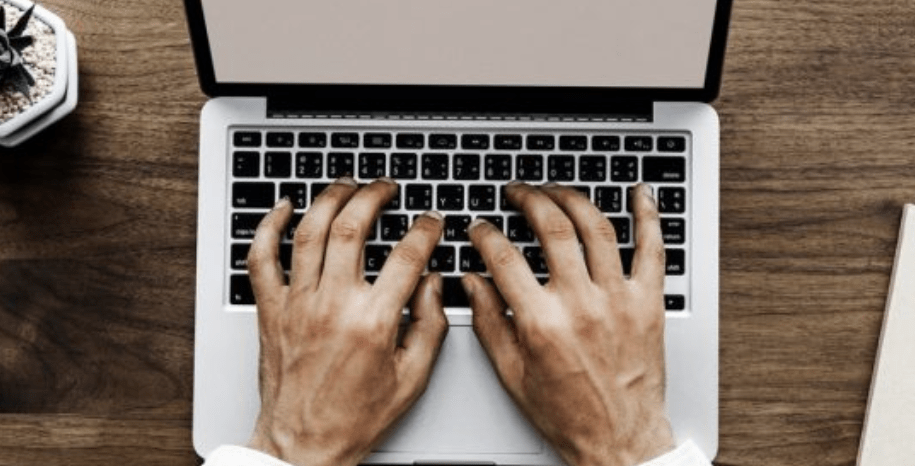 Man typing on laptop to help build and grow blog traffic.